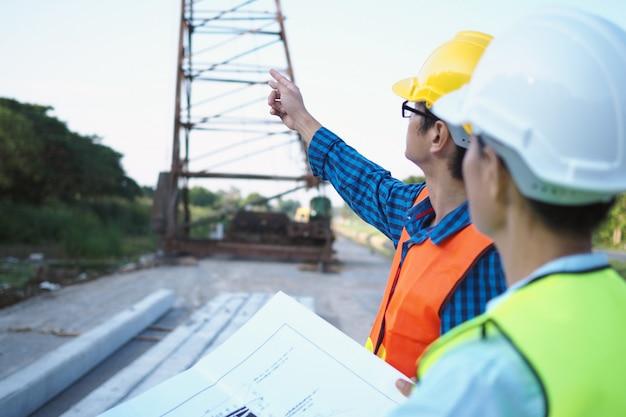 Engenheiros e empreiteiros estão discutindo planos de construção de casas.