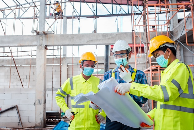 Engenheiros e trabalhadores da construção civil usando máscaras no trabalho