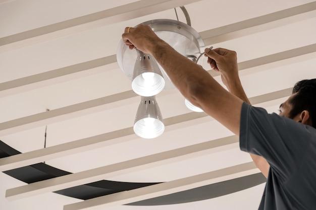 Engenheiros elétricos estão instalando lâmpadas de teto no corredor.