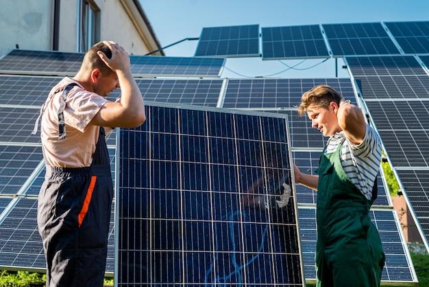 Engenheiros elétricos examinando a construção perto de baterias de energia solar, energia verde