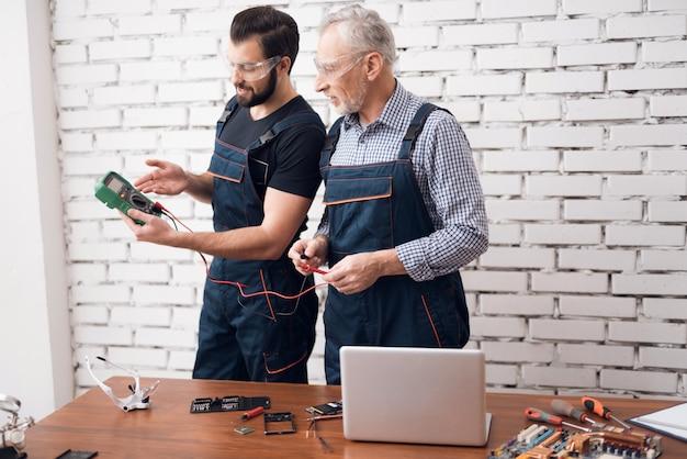 Engenheiros eletrônicos verificam o multímetro digital.