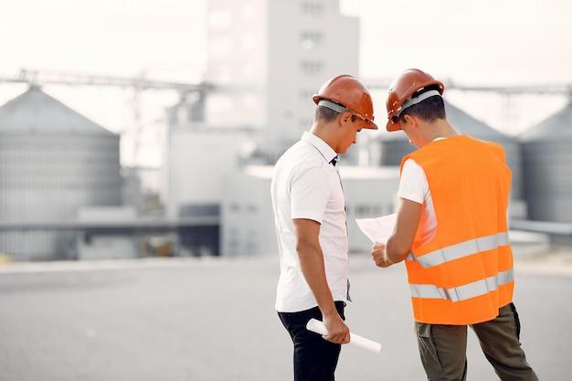 Engenheiros em capacetes de pé pela fábrica
