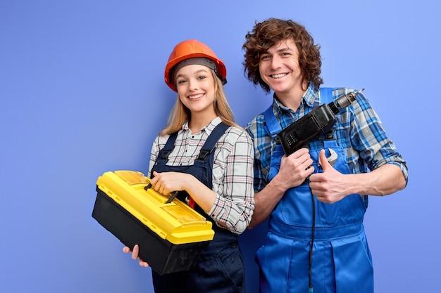 Engenheiros em macacões uniformes ficam com instrumentos de ferramentas posando isolados no azul