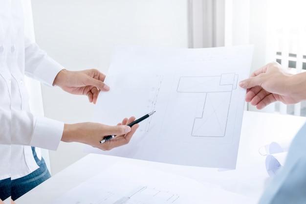 Engenheiros especializados / empresários que discutem um projeto de construção de edifícios no local de trabalho