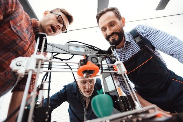 Engenheiros estão ao redor do dispositivo e eles estão felizes com o resultado