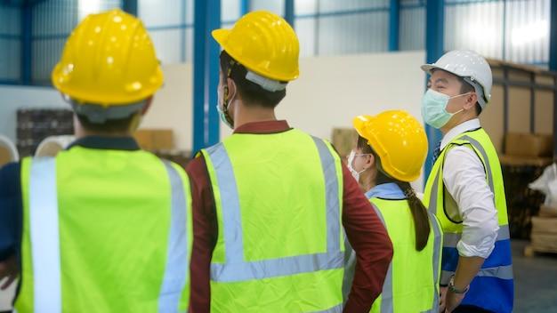 Engenheiros estão colocando um capacete de proteção na cabeça no armazém