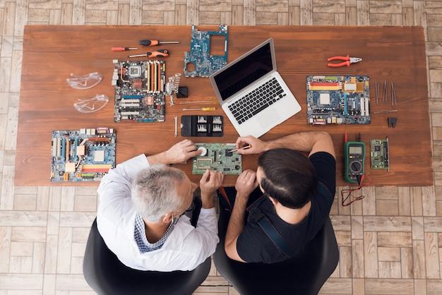 Engenheiros estão inspecionando gadget com estetoscópio.