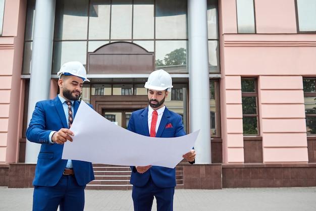 Engenheiros examinando um plano de construção juntos ao ar livre copyspace