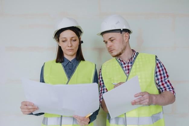 Engenheiros homens e mulheres com capacetes brancos e coletes de segurança amarelos no canteiro de obras para