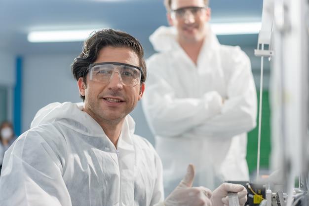 Engenheiros homens usam máquina de verificação e inspeção de epi na linha de produção de máscara na fábrica