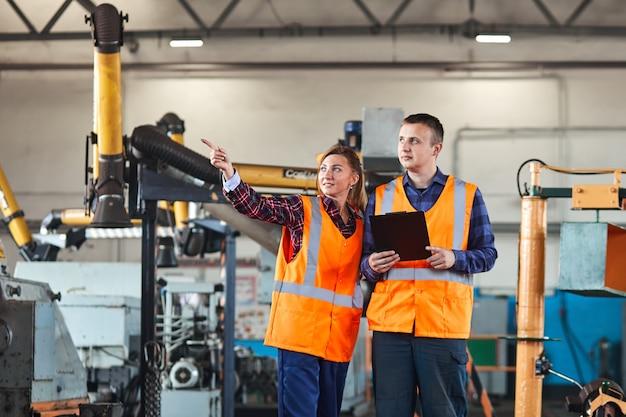 Engenheiros industriais masculinos e femininos têm uma discussão enquanto usam o tablet. eles trabalham em uma fábrica da indústria.