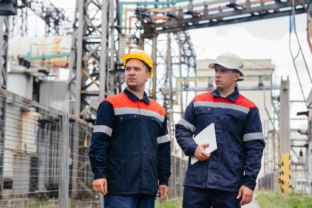 Engenheiros inspecionam a subestação elétrica