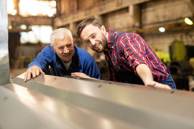 Engenheiros jovens e idosos em roupas de trabalho olhando uma grande peça metálica para uma nova máquina industrial durante o trabalho