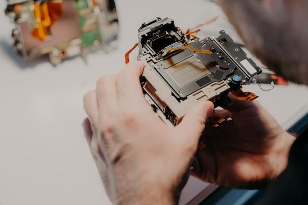 Engenheiros mãos detém câmera fotográfica quebrada