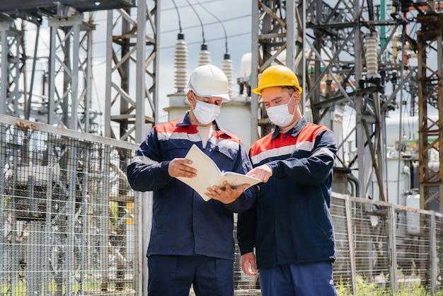 Engenheiros mascarados inspecionam uma subestação elétrica