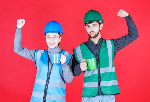 Engenheiros masculinos e femininos com capacete segurando canecas azuis e verdes e mostrando sinal de satisfação.
