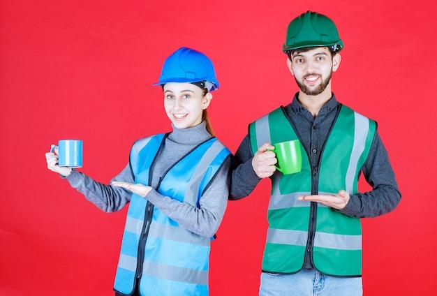 Engenheiros masculinos e femininos com capacete segurando canecas azuis e verdes.