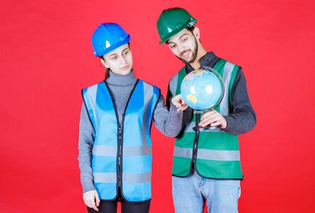 Engenheiros masculinos e femininos com capacetes segurando um globo do mundo e tentando encontrar locais nele.