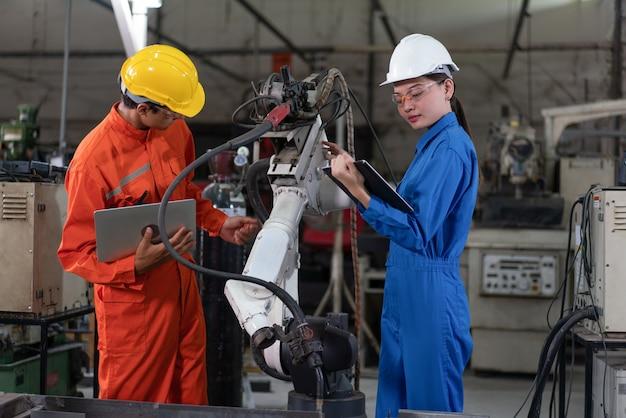 Engenheiros masculinos e femininos, inspeção, máquina de solda de braço robótico com um laptop na fábrica