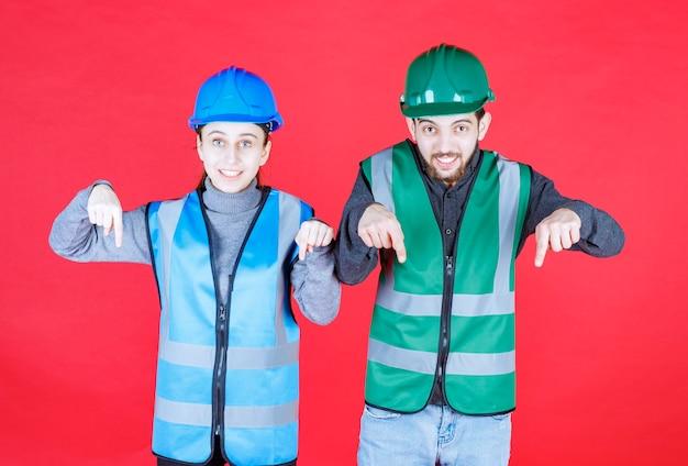 Engenheiros masculinos e femininos usando capacete e equipamento mostrando algo para baixo.