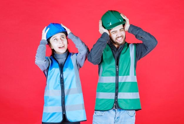 Engenheiros masculinos e femininos usando capacete e equipamento, segurando a cabeça com as duas mãos.