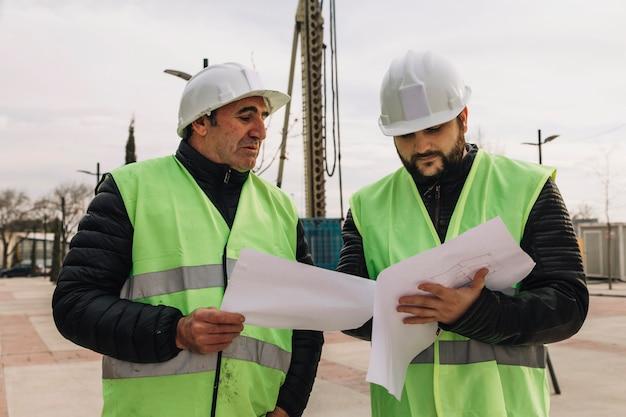 Engenheiros olhando rascunhos no canteiro de obras