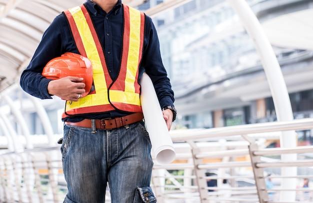 Engenheiros preparam-se para o trabalho com orange helmet e blue print.