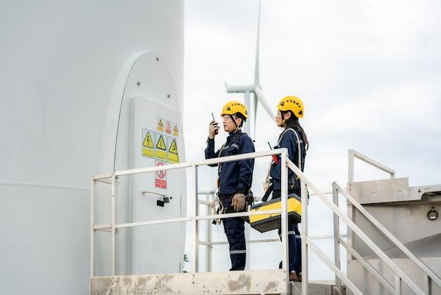 Engenheiros preparando e verificando o progresso de uma turbina eólica