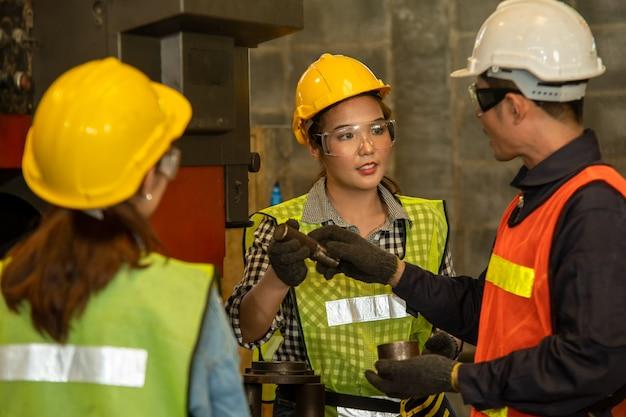 Engenheiros que trabalham na fábrica, equipe de trabalhadores e capataz verificando máquinas na fábrica.