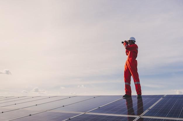Engenheiros reparando painel solar na geração de energia da usina solar; técnico em uniforme da indústria em nível de descrição de cargo na indústria