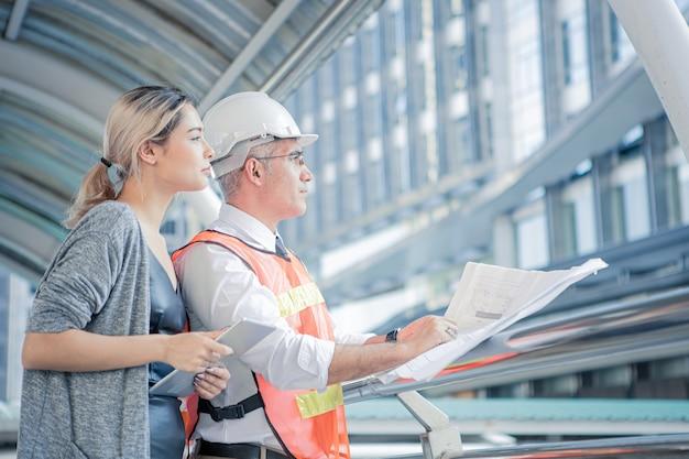 Engenheiros seniores descrevem os detalhes do projeto para jovens clientes no local de trabalho.