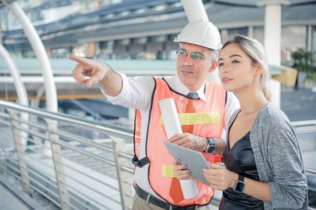 Engenheiros seniores descrevem os detalhes do projeto para jovens clientes.