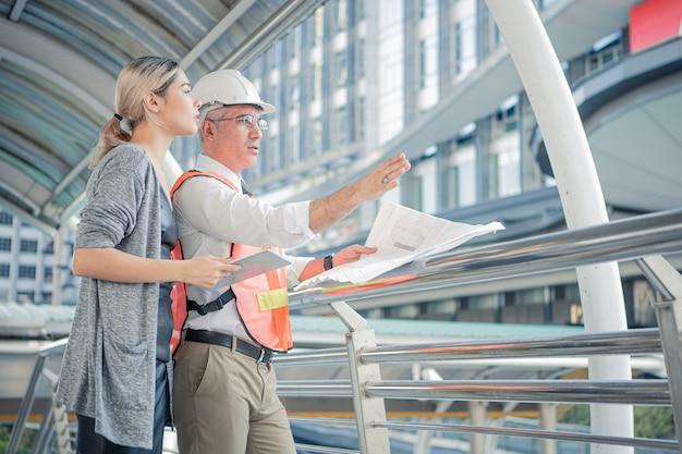 Engenheiros seniores descrevem os detalhes do projeto para uma jovem cliente no local de trabalho