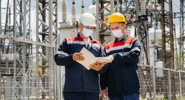 Engenheiros subestações elétricas conduzem uma pesquisa de equipamentos modernos de alta tensão na máscara