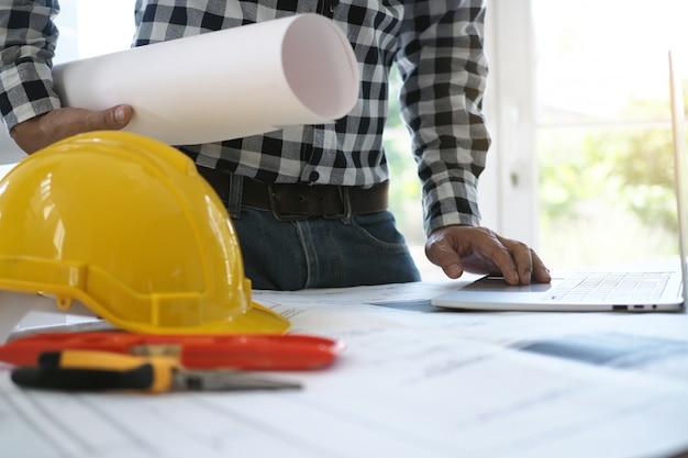 Engenheiros trabalham com laptops e blueprints