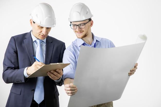 Engenheiros trabalhando com blueprint marcando edições em documentos na área de transferência