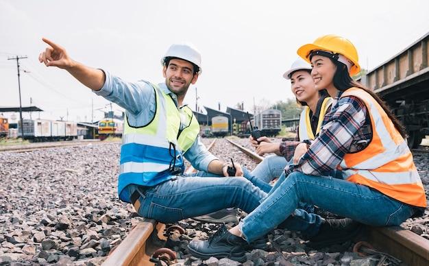 Engenheiros trabalhando e sentados na estação ferroviária