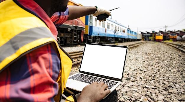 Engenheiros trabalhando na estação ferroviária de trem e segurando laptop com walkie-talkie para o projeto de plano parte traseira da liderança profissional do trabalho de engenharia