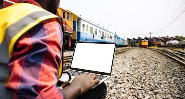 Engenheiros trabalhando na estação ferroviária de trem e segurando um laptop de tela branca para o projeto de plano