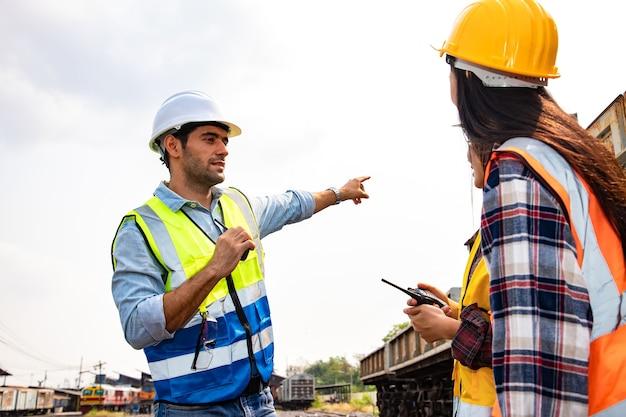 Engenheiros trabalhando na estação ferroviária e segurando laptop para planejamento e reunião