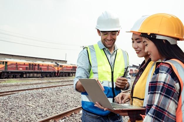 Engenheiros trabalhando na estação ferroviária e segurando um laptop