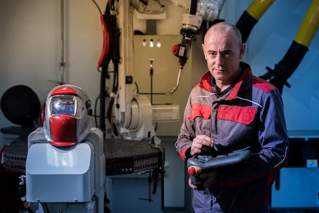 Engenheiros usando controle remoto de soldagem robótica na fábrica inteligente