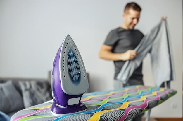 Engomar e empilhar roupas. ferro de engomar localizado na tábua de engomar colorida. no fundo está um homem que acabou de passar e começou a empilhar e separar a roupa lavada copie o espaço vazio