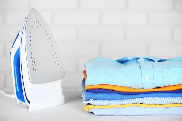 Engomar eletrônico e pilha de roupas a bordo na parede de tijolos