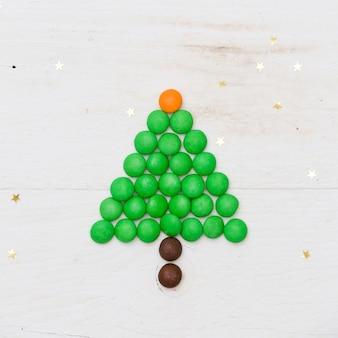 Engraçada árvore de natal feita de doces com pequenas estrelas douradas confetes em fundo branco de madeira