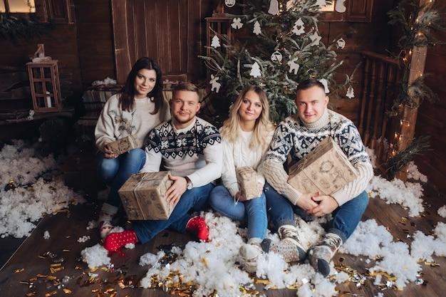 Engraçada companhia caucasiana de jovens amigos celebram o natal juntos, sentados perto da árvore de natal em um ambiente aconchegante