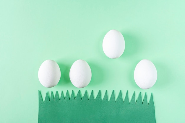 Engraçada engraçada composição de páscoa criativa com grama de papel verde e ovos brancos. diy e criatividade infantil. artesanato caseiro.