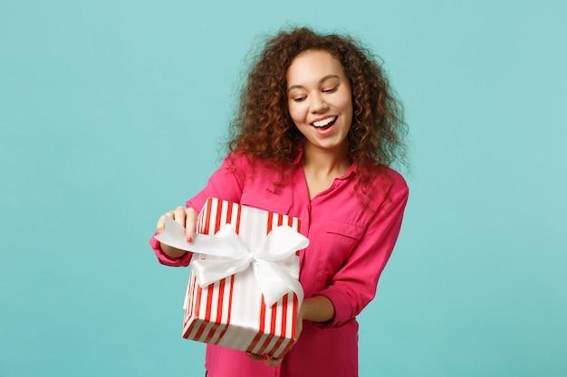 Engraçada garota africana com roupas casuais segura caixa de presente listrada vermelha com fita de presente isolada no fundo da parede azul turquesa. conceito de feriado de aniversário do dia internacional da mulher. simule o espaço da cópia.
