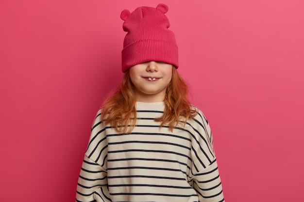 Engraçada menina ruiva se esconde atrás de um chapéu da moda, mostra dois dentes de leite, usa um macacão listrado casual, se diverte dentro de casa, isolada na parede rosa, sendo uma criança travessa. conceito de infância feliz
