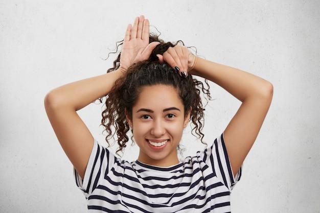 Engraçada modelo feminina tem cabelos crespos, tolinha sozinha, finge ser coelhinha ou gatinha, faz orelhas com as mãos.